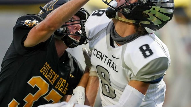 Westerville Central's Luke Swaney tries to get free as Upper Arlington's Adam Cipriano is called for pass interference Aug. 28.