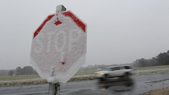 A sport utility vehicle passes by a stop sign covered in snow at Occohannock Elementary School in Exmore, Va.
