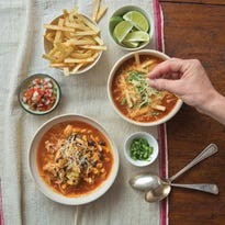 Mexican tortilla chicken soup is scented with chilies and spices, and served with an assortment of garnishes.