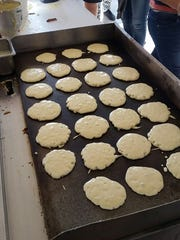 A griddle full of pancakes cooks Monday at Oñate High School, where staff and volunteers cooked hot cakes for students in advance of the start of standardized testing. The group expects to cook about 7,200 pancakes as testing continues over the next three weeks.