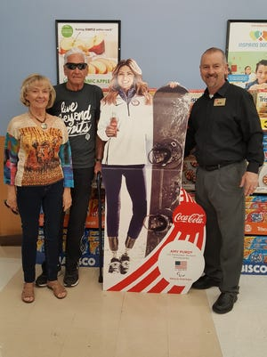 Gene and Connie Campbell with Alan Rasmussen of Smith's pose next to cardboard cutout of the Campbells' granddaughter, U.S. Paralympian Amy Purdy