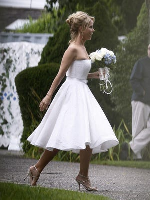 Actress Cheryl Hines wears a Romona Keveza cocktail-length dress as she walks across to the tent at her wedding to Robert F. Kennedy Jr., in Hyannis Port, Mass., on Aug. 2, 2014. Designers are offering a greater range of shorter styles as more brides break from tradition and personalize their wedding dresses.