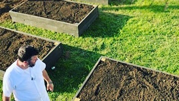 Chef Todd Fuller of The Farm & Fisherman Tavern in Cherry Hill looks over the restaurant's garden beds.
