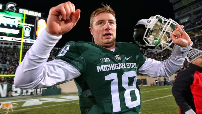 Michigan State quarterback Connor Cook celebrates a win against Penn State last month at Spartan Stadium. Cook's attitude and leadership have come under fire lately.