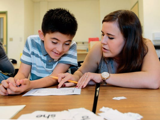 Teacher Miriam Bencomo helps John Michael Terrazas on Wednesday with an assignment.