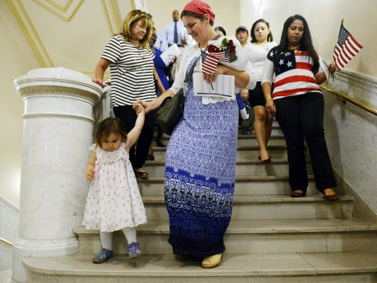 Lynn Lemon-Witmer of Dover Township holds her 2-year-old daughter Grace Witmer's hand as they and others walk down the stairs for the naturalization ceremony at the York County Administrative Center on Thursday. Thirty-five people representing 23 countries took oaths to become naturalized citizens. Lemon-Witmer is originally from South Africa.