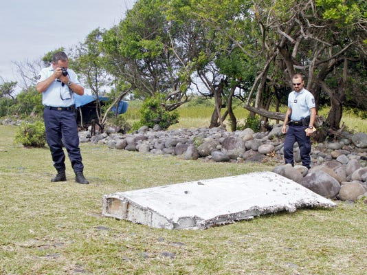 "In this photo dated Wednesday, July 29, 2015, French police officers look over a piece of debris from a plane in Saint-Andre, Reunion Island. Air safety investigators, one of them a Boeing investigator, have identified the component as a ""flaperon"" from the trailing edge of a Boeing 777 wing, a U.S. official said. Flight 370, which disappeared March 8, 2014, with 239 people on board, is the only 777 known to be missing. (AP Photo/Lucas Marie)"