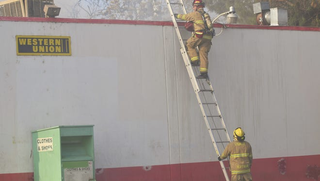 Firefighters make sure there is no damage to Cheaper Gas and Food on the corner of Houston Avenue and Court Street.