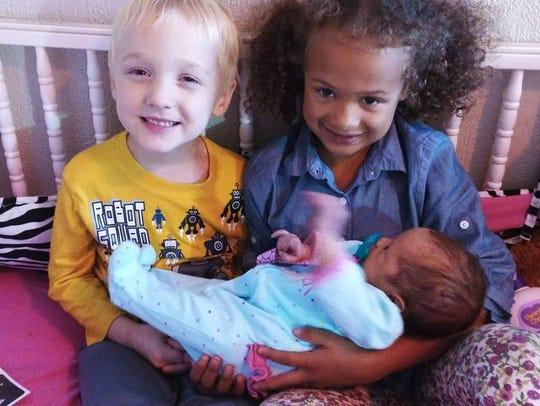 Kayla Britton's children Grayson and Zakaia hold  baby