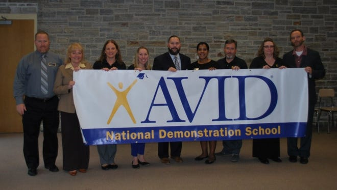 (From left) Clay Stewart, AVID Northeast program manager; Maggie Colina-Sanchez, district language arts supervisor; Kim Hallenbeck, AVID district director; Sandy Lokuta, AVID coordinator; David Gentile, Millville Public Schools superintendent; Jinan O'Connor, AVID Northeast States director; Steven Price, Lakeside principal; Beth Benfer, instructional coach and AVID site coordinator; and Tim Bugno of the AVID Center hold a banner announcing Lakeside Middle School was selected as a National Demonstration School by AVID.
