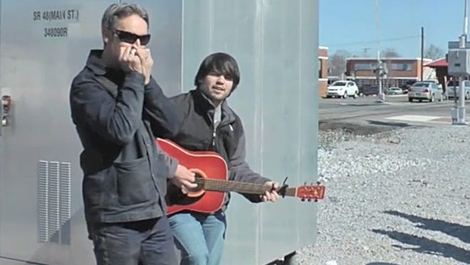 American Pickers star Mike Wolfe, left, plays harmonica while a crew member does a different kind of picking near Holland Park in downtown Dickson.