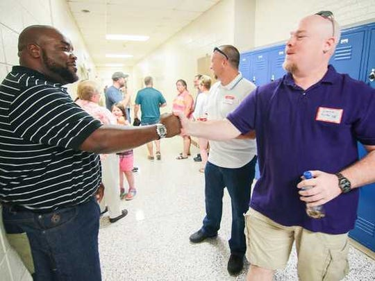 Jarvis Blanding (left), class of 1996, shakes hands with Donnie Kirby, class of 1993, during the McDuffie High School reunion of classes at the school in Anderson. Former McDuffie students represented most of the classes from 1965 to when the school closed in 1996.
