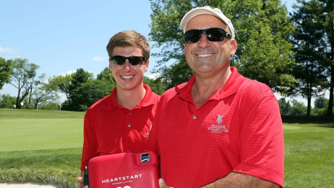 Jimmy Gilchrist, left, and Dave Solomon stand at the 16th green where they helped save a 78-year-old New Jersey golfer who had a heart attack last Tuesday while playing the hole at Putnam County Golf Course. Dave used the AED pictured.