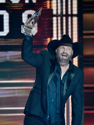 Garth Brooks hoists his Entertainer of the Year award during the CMA Awards on Wednesday, Nov. 8, 2017, at Bridgestone Arena in Nashville.