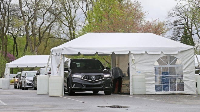 Cars line up for a Kroger drive-through COVID-19 testing site earlier this year at the Franklin Park Conservatory in Columbus.