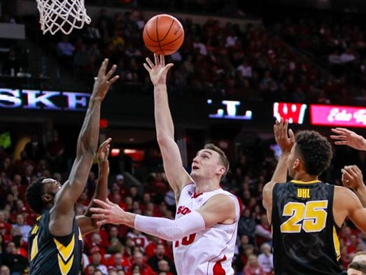 Wisconsin's Sam Dekker, center, shoots between Iowa's