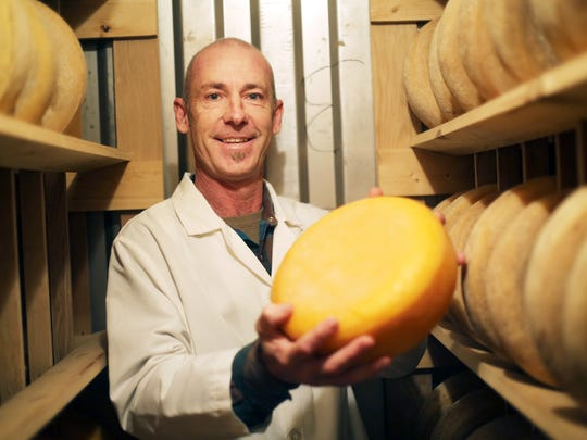Rod Volbeda with a wheel of a raw-milk Gouda in the aging room at Willamette Valley Cheese Company.