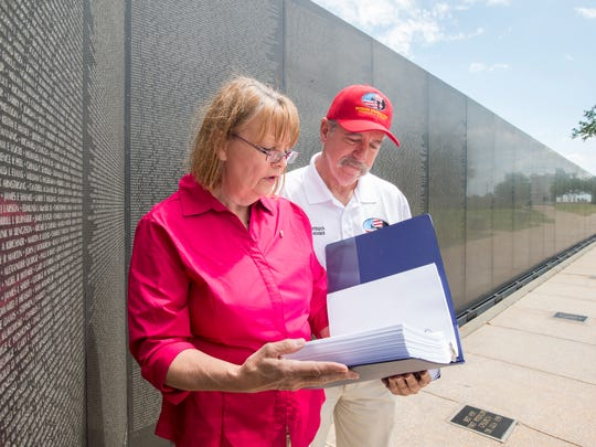 Jill Hubbs, WSRE's director of education and outreach, and Paul Entrekin, Veterans Memorial Park board member, look through one of two binders with all of the names listed on the Wall South at Veterans Memorial Park in Pensacola on April 27.