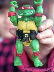 "An unidentified girl holds ""Raphael"", one of the four Teenage Mutant Ninja Turtles in Boston, Dec. 12, 1998. The turtles were created by Peter Laird and Kevin Eastman."