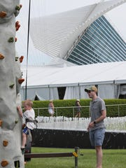 Justinn Tanem of Wauwatosa (right) watches his son climb the rock climbing wall. It was one of the hands-on activities available for children at the Lakefront Festival of Art.