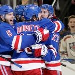 Rangers players share a group hug after Dominic Moore scored the only goal of Thursday night's game.