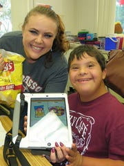 The students and teachers were all smiles while demonstrating how the iPads are being used as communication devices for the children.