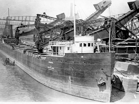 This historical photo provided by a diver shows the Hydrus freighter at a unnamed port being loaded with iron ore.