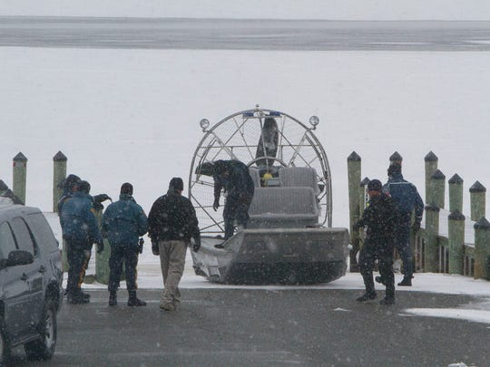 State Police officers in Pine Beach prepare an ice boat for a search for a pickup truck that crashed through the ice of the Toms River early Sunday. Divers located the truck later in the day and found the body of a dog but no human occupants.