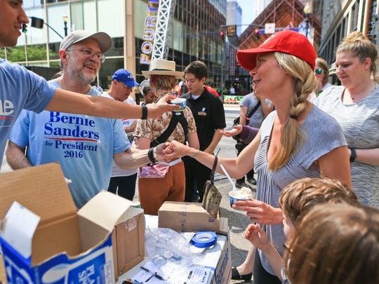 Mary Beth Legler squeezes the hand of Ben & Jerry's co-founder Jerry Greenfield Wednesday afternoon at the corner of 4th Street and Muhammad Ali while Greenfield was passing out free ice cream and stumping for Bernie Sanders in downtown Louisville.