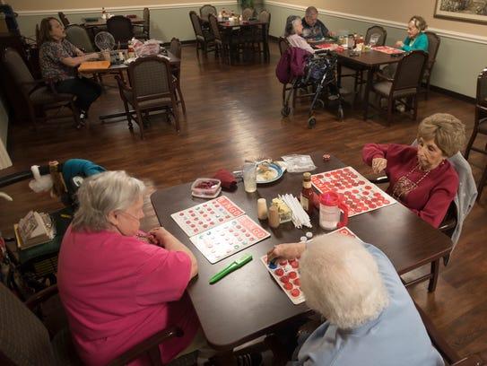 Several residents in Hopeton Village play bingo in