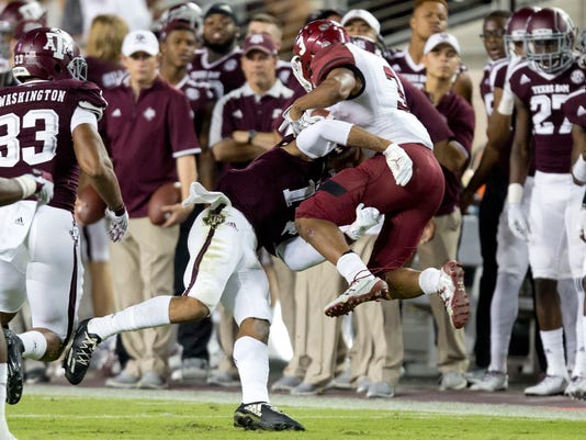 Texas A&M's Justin Evans (14) tackles New Mexico State's Larry Rose III (3) for a short gain during the second quarter of an NCAA college football game Saturday, Oct. 29, 2016, in College Station, Texas. (AP Photo/Sam Craft)