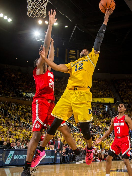 Michigan guard Muhammad-Ali Abdur-Rahkman (12), defended by Ohio State forward Andre Wesson (24), attempts a basket in the second half of an NCAA college basketball game at Crisler Center in Ann Arbor, Mich., Sunday, Feb. 18, 2018. (AP Photo/Tony Ding)
