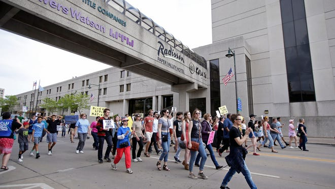 People protesting the fatal police shooting of Jimmie M. Sanders walk along College Avenue from Houdini Plaza to Jack's Apple Pub on May 27 in Appleton.