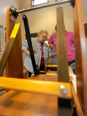 Lynn Reimer of Shelby demonstrates how to use a drum carder Friday afternoon during the Malabar Spinning & Weaving Guild  Fall Fiber Art Show at the visitors center.