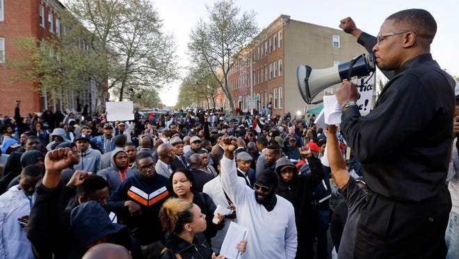 Malik Z. Shabazz, right, of Black Lawyers for Justice, speaks to a group of protesters outside the Baltimore Police Department's Western District police station during a protest march for Freddie Gray, Wednesday, April 22, 2015, in Baltimore. Gray died from spinal injuries about a week after he was arrested and transported in a police van. (AP Photo/Patrick Semansky)