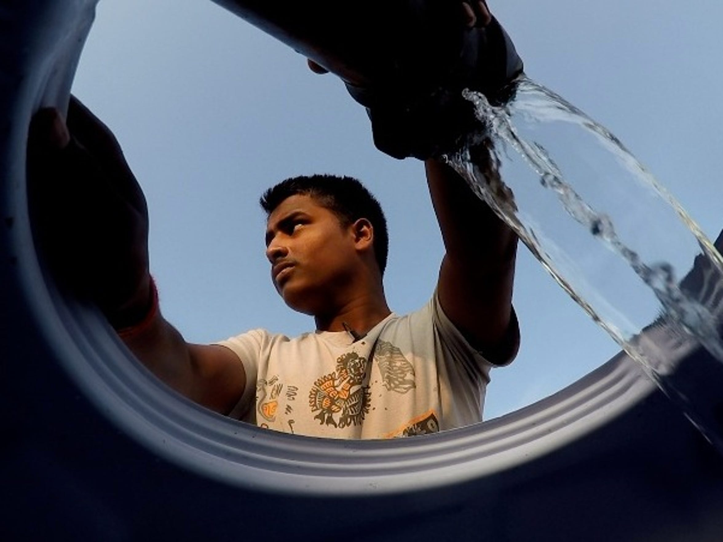 Mukindra Suryawanshi, 22, fills his family's water tank in Maharashtra state in western India. He and his relatives carry the tank on an ox cart and fill it up at another farmer's irrigation well. The water, drawn from about 850 feet underground, is used for washing, cooking and bathing by an extended family of 22 people.