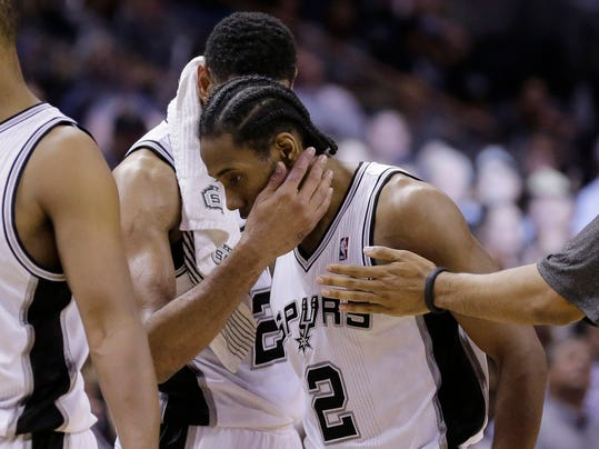 San Antonio Spurs' Kawhi Leonard (2) is hugged by teammate Tim Duncan during the second half of Game 5 of a Western Conference semifinal NBA basketball playoff series, Wednesday, May 14, 2014, in San Antonio. San Antonio won 104-82. (AP Photo/Eric Gay)