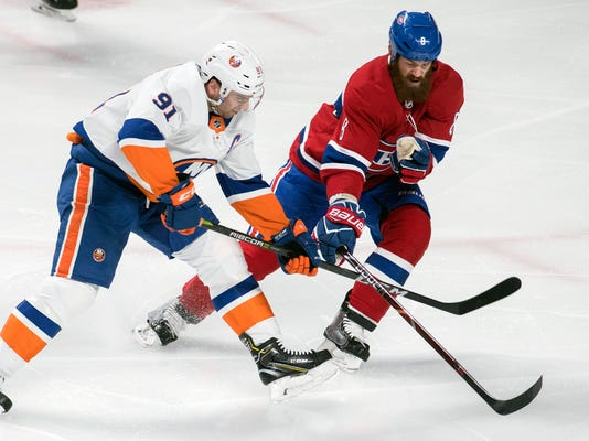 Montreal Canadiens' Jordie Benn (8) and New York Islanders' John Tavares (91) battle for the puck during the first period of an NHL hockey game Wednesday, Feb. 28, 2018, in Montreal. (Graham Hughes/The Canadian Press via AP)