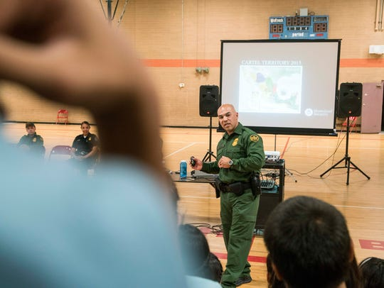 Border Patrol agent Cesar Gongalez talks to students