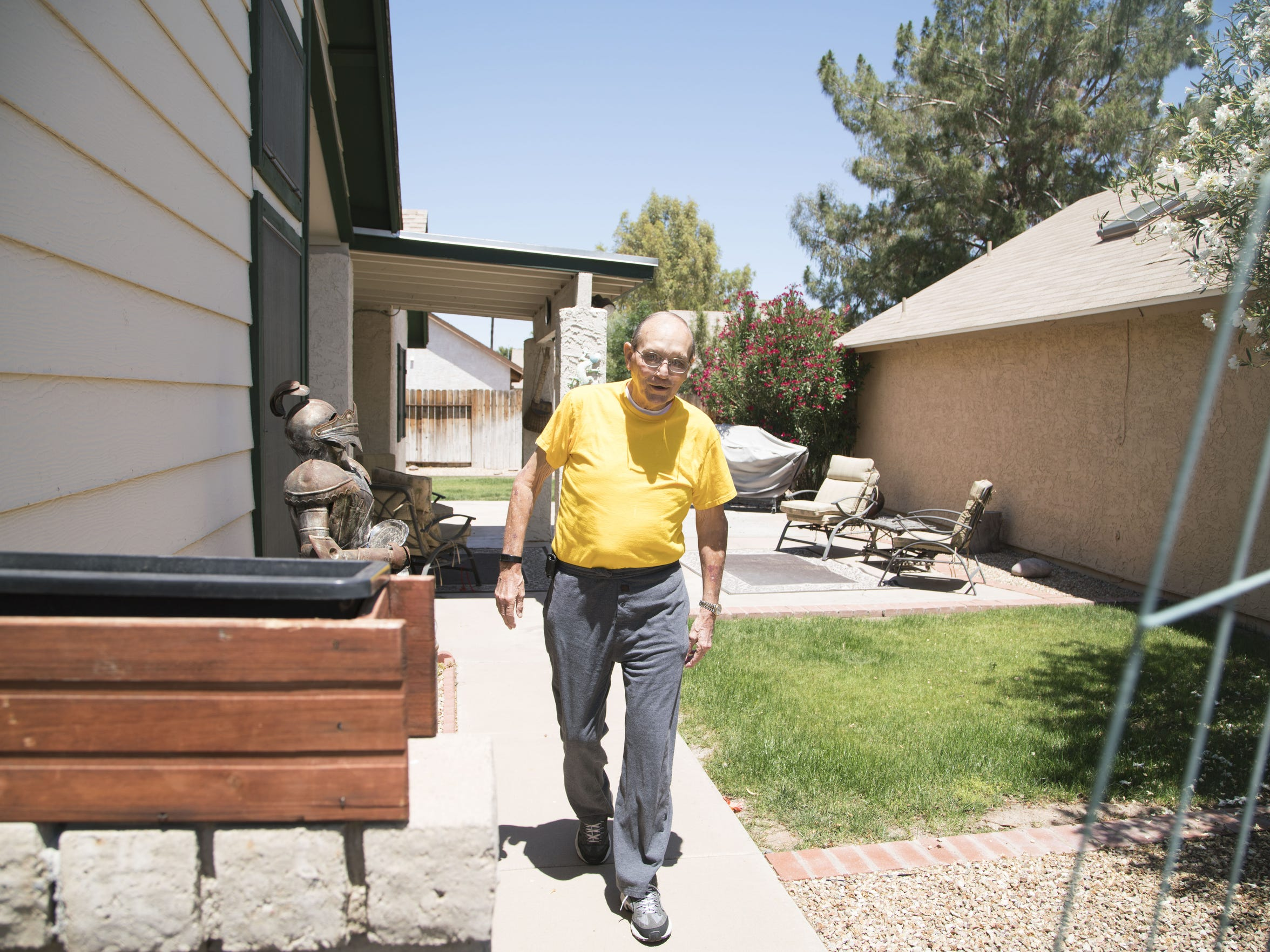Harvey walks outside his Mesa home.