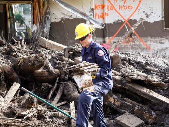 Montecito firefighter Ryland McCracken carries muddy