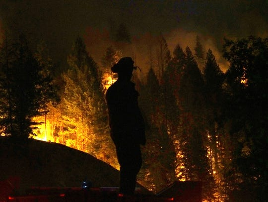 Firefighter Derek Longoria stands atop his engine while