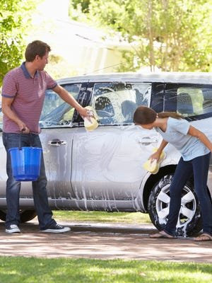 Father And Teenage Daughter Washing Car Together With A Bucket And Sponge.