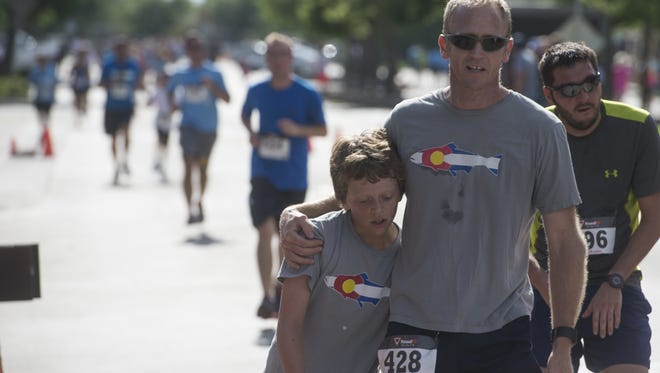 An exhausted Dylan Whitesell, 12, leans into his father, Justin, after the two crossed the finish line at the Father's Day 5K Sunday, June 21, 2015. Hundreds celebrated Father's Day by participating in the event.