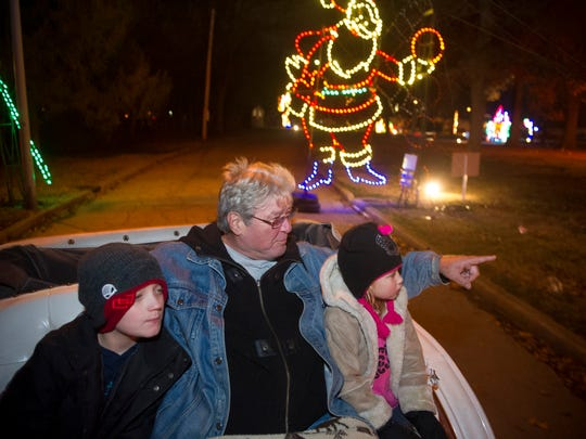 Tyler Burnham, 10, from left, rides in a horse drawn carriage with his grandfather, Faxson Cockrell, and sister, Sophia Burnham, 6, all of Hopkinsville, Ky., during Ritzy's Fantasy of Lights at Garvin Park in Evansville, Friday, Nov, 25, 2016. The event is put on by the Easterseals Rehabilitation Center and runs through Jan. 1.