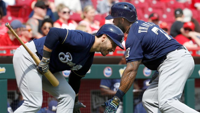 Brewers first baseman Eric Thames celebrates with Ryan Braun after Thames' home run Sunday vs. the Reds.