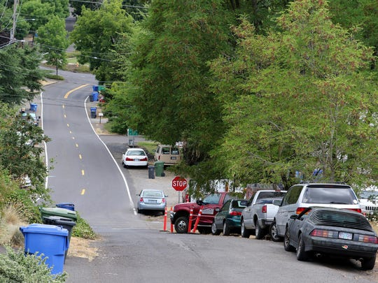 Cars are parked July 16 along a steep section of Bluff Street SE near the Bluff Apartments as renovations continue to the HUD senior and disabled housing.