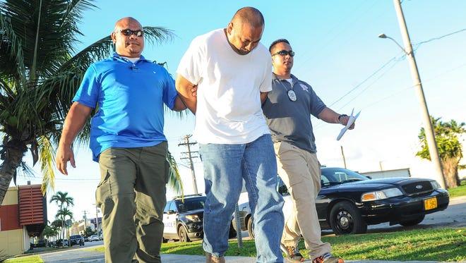 Jay Ignacio Quinata, center, is escorted into the Guam Police Department's Hagåtña precinct upon his arrest on Friday, July 8.