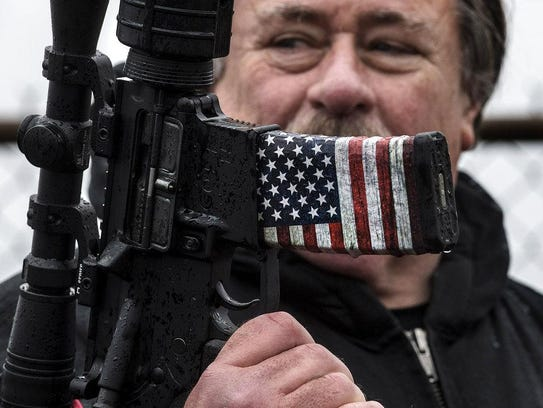 Clark Albritton holds his AR-15 during a counter protest