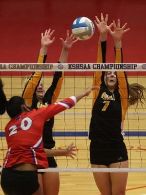 Bishop Miege's Leilani Elder (20) spikes the ball to Andale's Annabeth Baalmann (10) and Jaley Eck (7) during their championship game in the Class 4A state volleyball tournament Saturday evening at the Sports Arena in Hutchinson. Bishop Miege defeated Andale 25-23, 25-13.